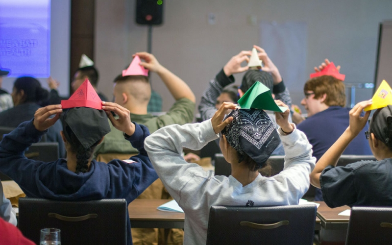 Students display their paper hat making abilities in a lesson that  highlights differences between economic systems.