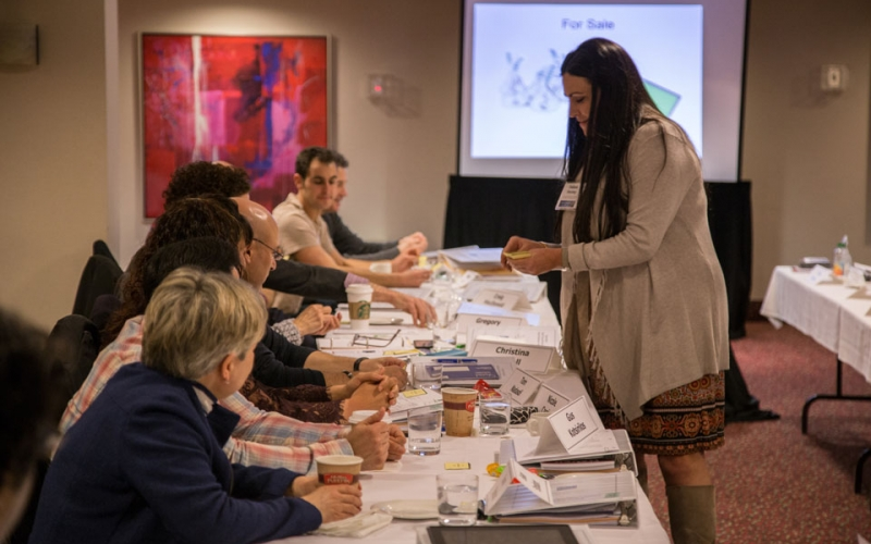 Teachers join instructor Debbie Henney in an activity that aims to teach the concept of inflation