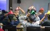 Students display their paper hat making abilities in a lesson that  highlights differences between economic systems